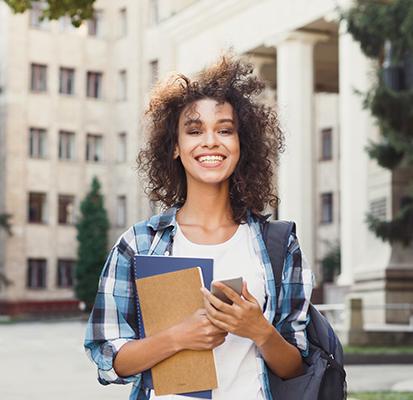 Garota sorrindo segurando caderno